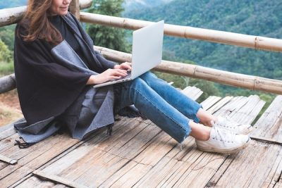closeup of woman working on laptop on wooden balcony against green mountain background