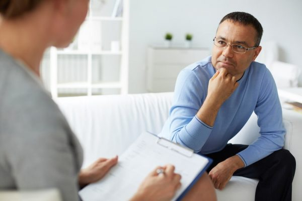 male patient listening to psychologist