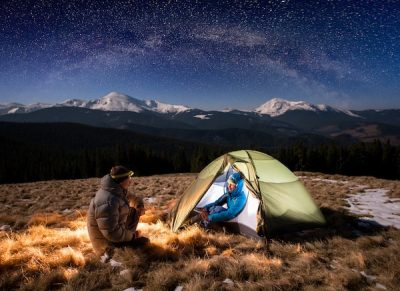 couple winter camping under night stars and snow mountains in background