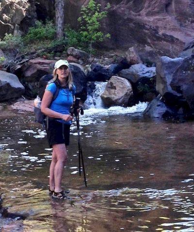 Marlo Bennett hiking through creek